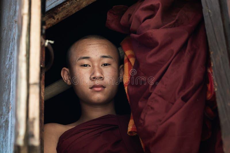 Nyaungshwe, Myanmar - April 2019: portret van een jonge beginner Boeddhistische monnik die uit het venster kijken stock foto's