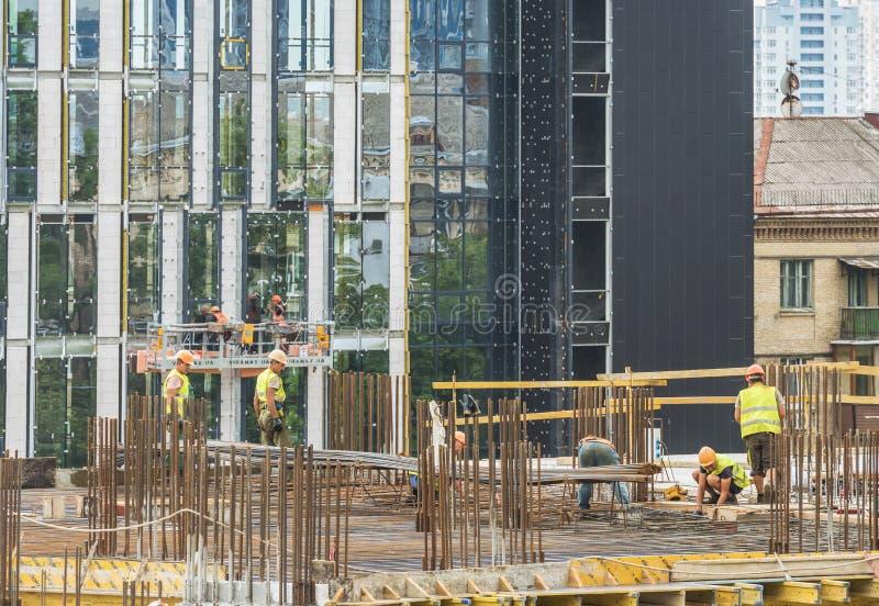 Nybygge under konstruktion och konstruktionsplats av en bostads- byggnad Arbetare av olika specialiteter arbetar på platsen arkivfoton