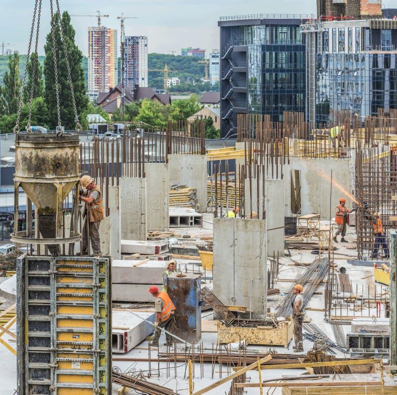 Nybygge under konstruktion och konstruktionsplats av en bostads- byggnad Arbetare av olika specialiteter arbetar på platsen royaltyfri fotografi