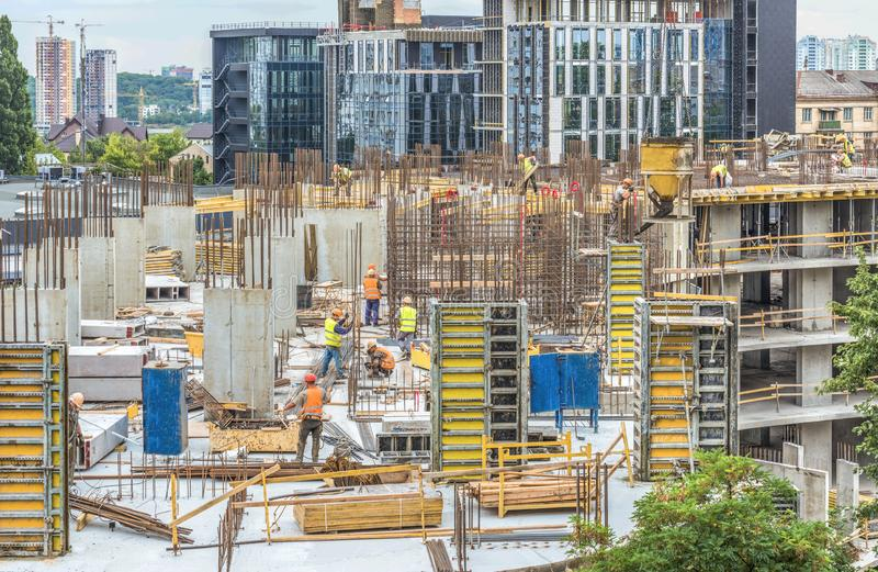 Nybygge under konstruktion och konstruktionsplats av en bostads- byggnad Arbetare av olika specialiteter arbetar på platsen arkivbild
