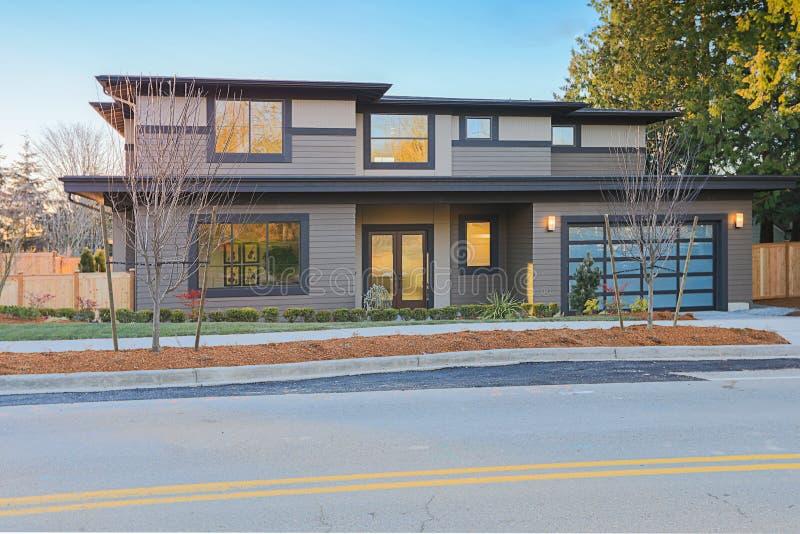 Nybyggnadhem med den låga lutningstak- och bruntsidingen arkivfoto