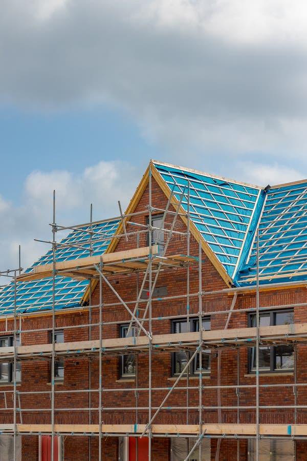 Nybyggt hem med det lutade taket, material till byggnadsställning, konstruktionsplats arkivfoton
