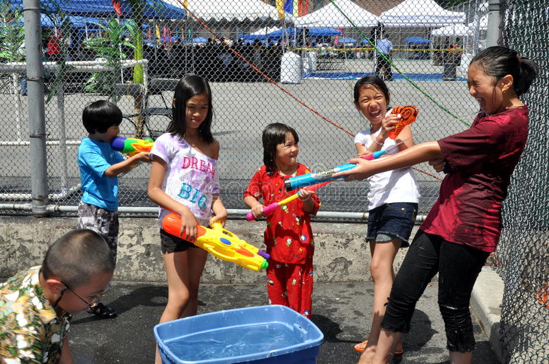 NYC: Burmese Water Festival. Children playing with water guns give each other a good soaking at the annual Burmese Thingyan Water Festival in New York City stock photo