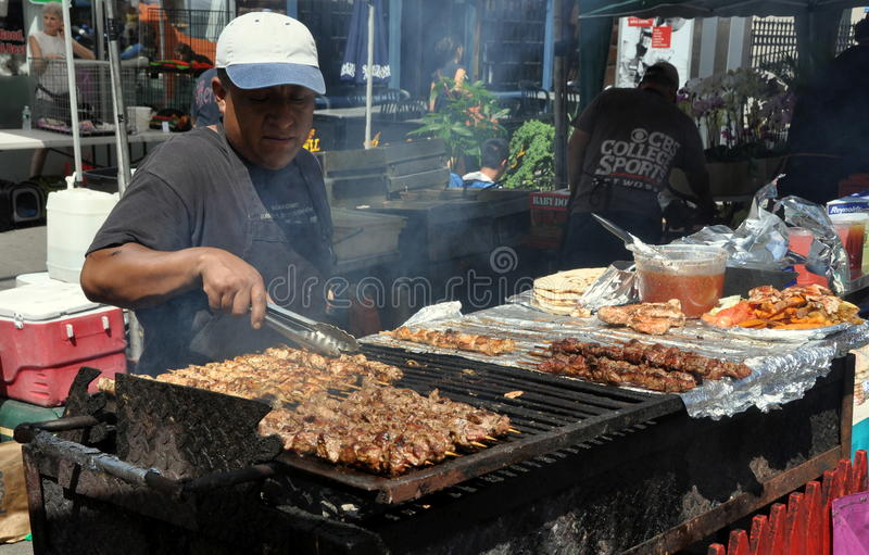 NYC: Cook Grilling Meats. Cook at work grilling meats on an outdoor barbecue at the annual Amsterdam Avenue Street Festival on Manhattan's Upper West Side in New royalty free stock photography