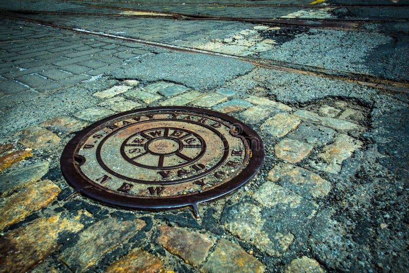 NYC-Einsteigeloch-Abflussabdeckung stockbild