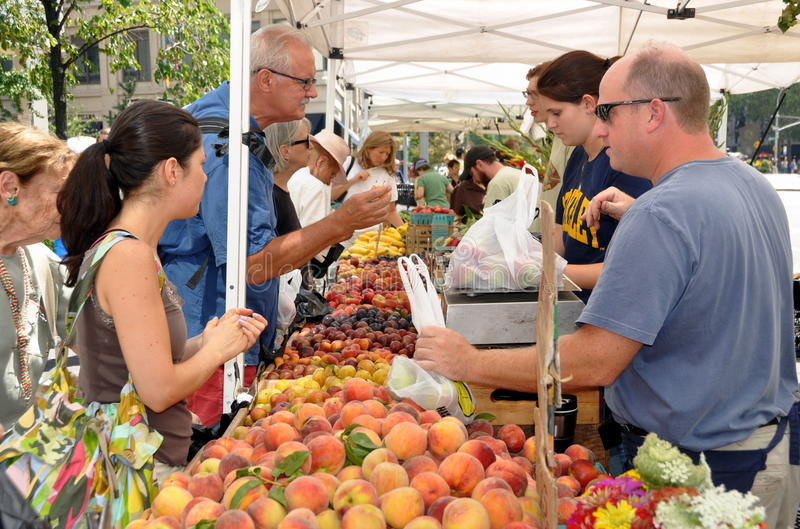 NYC: Lincoln Square Farmer's Market. Shoppers buying fresh fruits from a farm stand at the Lincoln Square Farmer's Market on Broadway at 66th Street in New York stock image