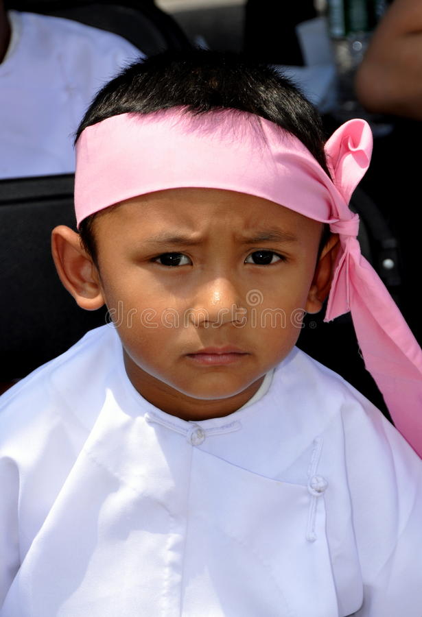 NYC: Little Burmese Boy. A little Burmese boy wearing a traditional pink headband with large bow and a white robe at the annual Burmese Thingyan Water Festival stock image