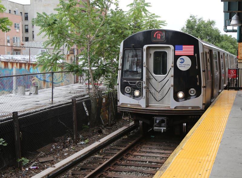 NYC-Metroq Trein die bij de Post van de Koningenweg in Brooklyn aankomen stock afbeelding