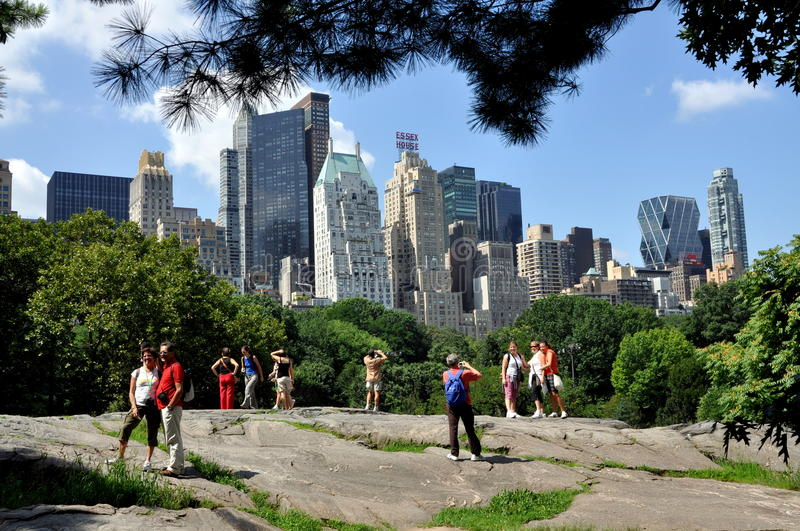 NYC: Midtown Skyline from Central Park. Tourists taking photos and admiring the dramatic midtown Manhattan skyline from a viewpoint atop a rock in Central Park royalty free stock image
