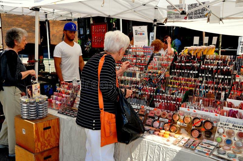 NYC: Mulher que compra Costmetics na feira da rua fotos de stock