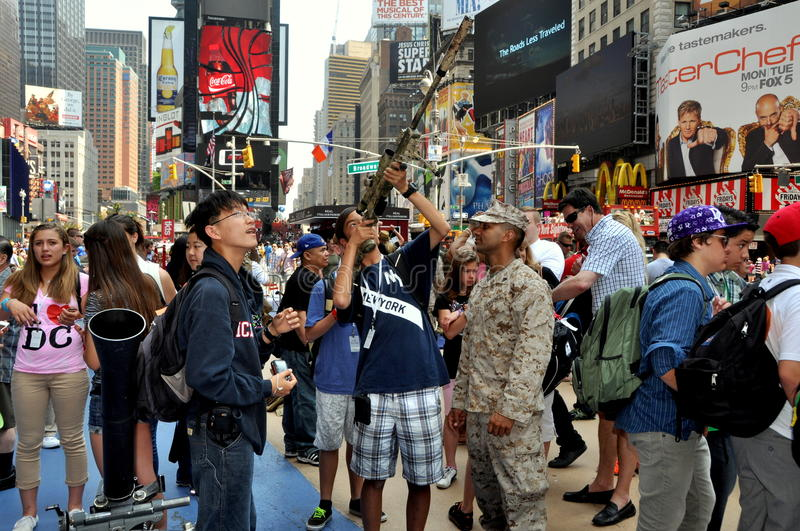 NYC: Soldier with Tourists in Times Square. Tourists learn how to aim a high-powered rifle from a U.S. Army soldier dressed in fatigues during Fleet Week royalty free stock photography