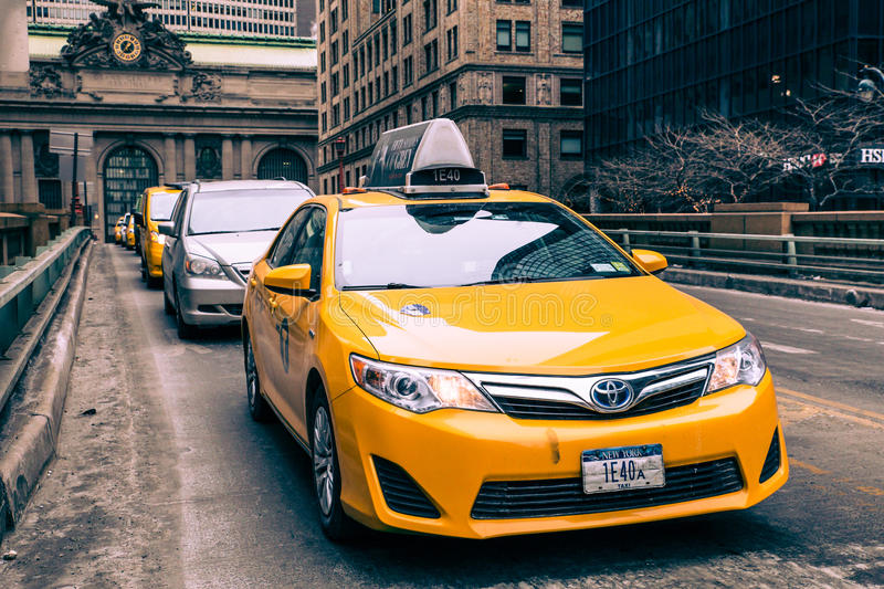 NYC Taxi in Midtown Manhattan. NEW YORK CITY - FEBRUARY 21, 2015: View of yellow taxi and cars on Park Avenue in midtown Manhattan with Grand Central Terminal in stock photography