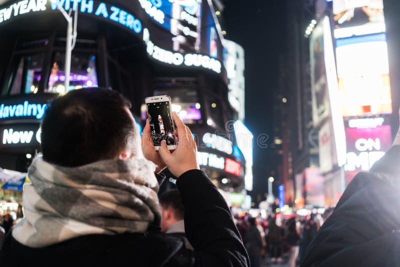 NYC/USA 31 DEZ 2017 - homme à photographier dans la Times Square la nuit image libre de droits
