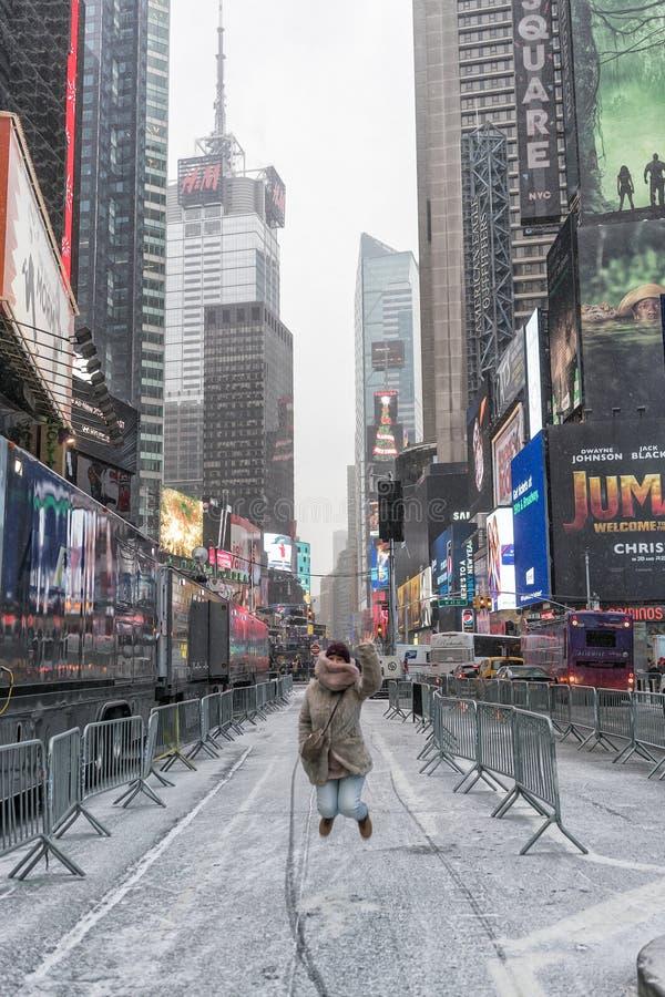 NYC/USA - 29 DEZ 2017 - moça que salta nos Times Square com neve imagem de stock royalty free