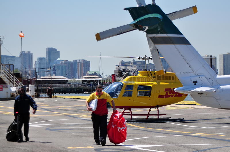 NYC: West 30th Street Heliport. Two men pulling bags across the tarmac just delivered by a DHL helicopter at the West 30th Street Heliport on Manhattan's West stock image