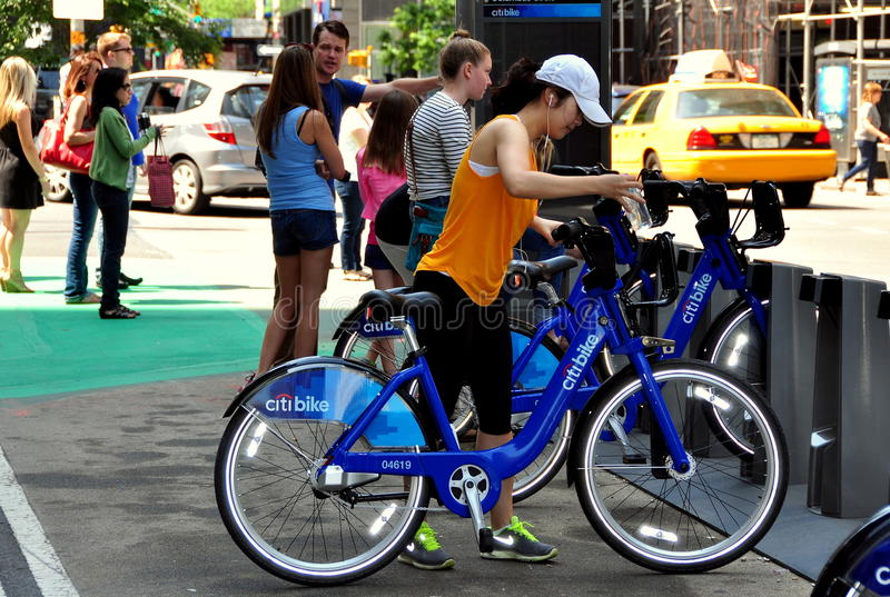 NYC: Woman with Citibike at Docking Station. Woman checking out one of the brand new Citibikes from a docking station at 56th Street and Broadway in NYC stock photos