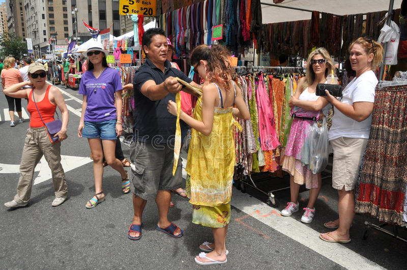 NYC: Woman at Street Festival. A vendor helps style one of his garments for a potential customer at this stand at a summer Broadway street festival in the West royalty free stock photo