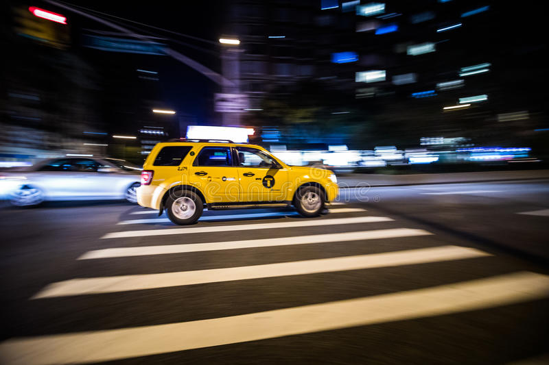 NYC Yellow Cab passing Fast at Night in Manhattan, New York. stock image