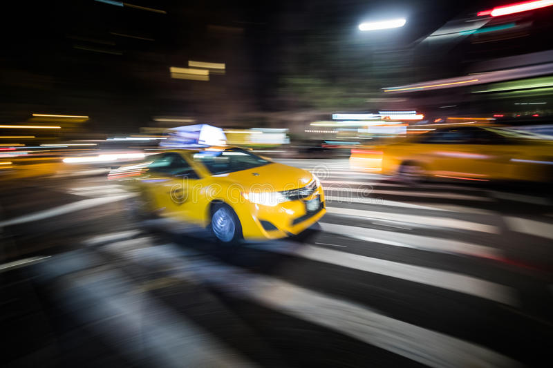 NYC Yellow Cab passing Fast at Night in Manhattan, New York. royalty free stock images