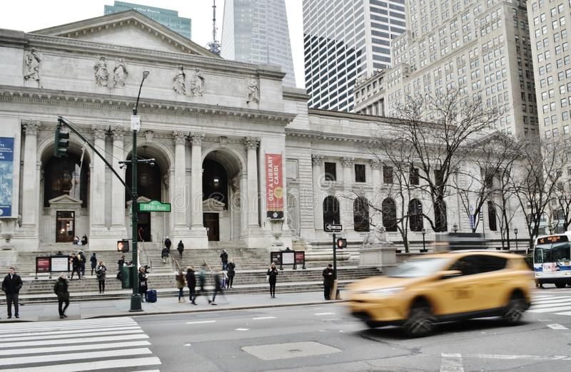 NYC Yellow Taxi Cab in Midtown Manhattan New York Public Library Building royalty free stock photo