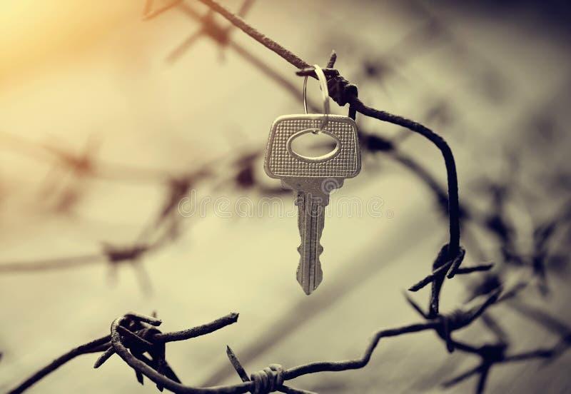 Nyckel- hängningar på försett med en hulling ett rostigt - tråd royaltyfria bilder