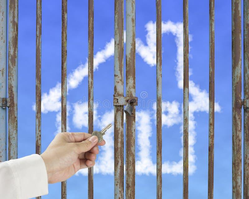 Nyckel- låsande upp låst dörr för handhåll med molnhuset i blå himmel arkivfoto