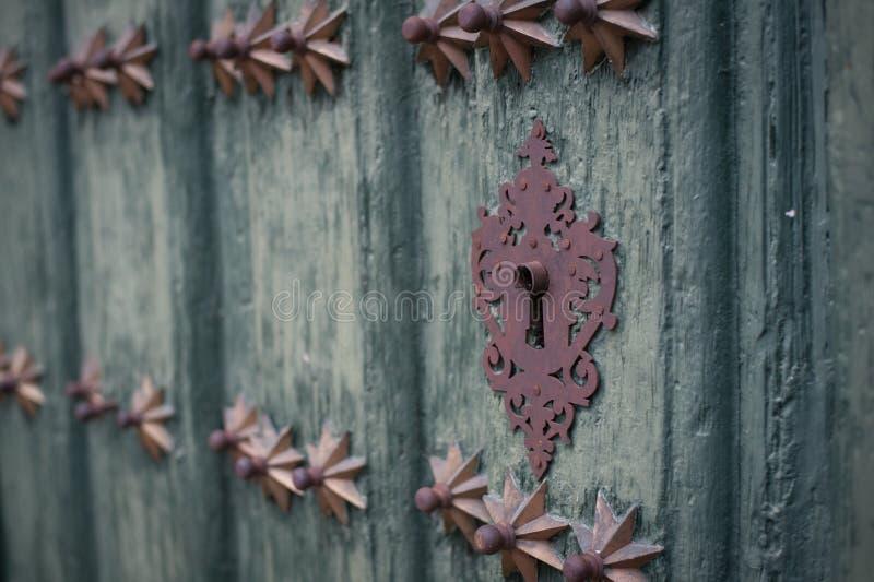 Nyckelhål i en gammal paneled trädörr royaltyfri fotografi