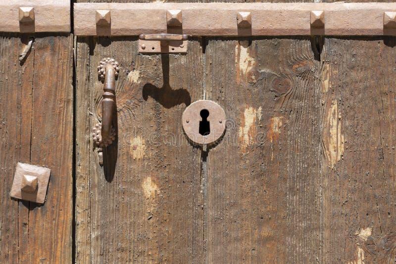 Nyckelhål i en gammal paneled trädörr med det antika dörrhandtaget; arkivfoto