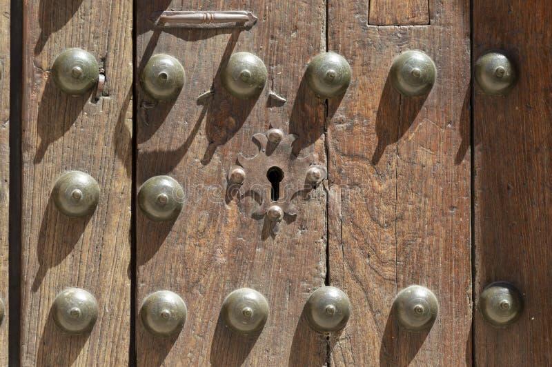 Nyckelhål i en gammal paneled trädörr med det antika dörrhandtaget arkivfoton