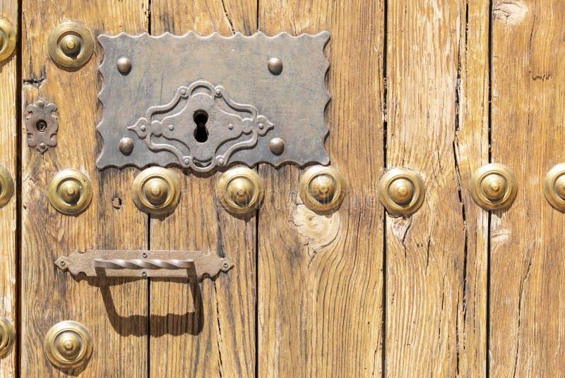 Nyckelhål i en gammal paneled trädörr med det antika dörrhandtaget; royaltyfria bilder