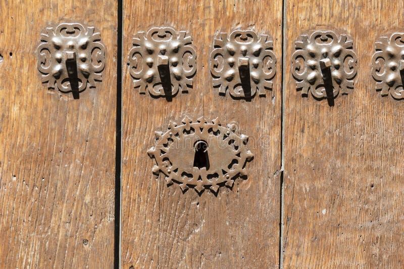 Nyckelhål i en gammal paneled trädörr med det antika dörrhandtaget; royaltyfri fotografi