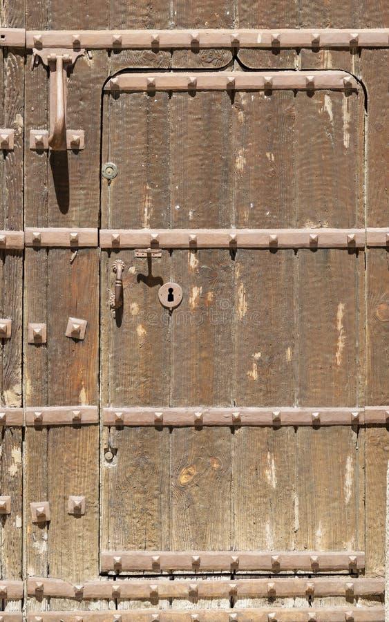 Nyckelhål i en gammal paneled trädörr med det antika dörrhandtaget; rostigt och ridit ut royaltyfria foton