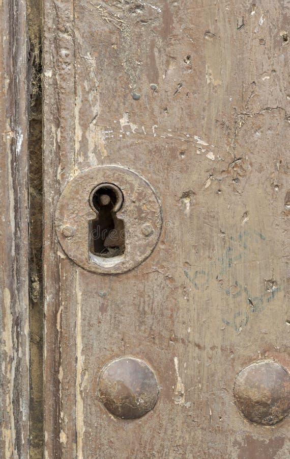 Nyckelhål i en gammal paneled trädörr; arkivbild