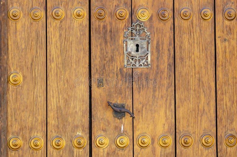 Nyckelhål i en gammal paneled trädörr; rostigt arkivfoto