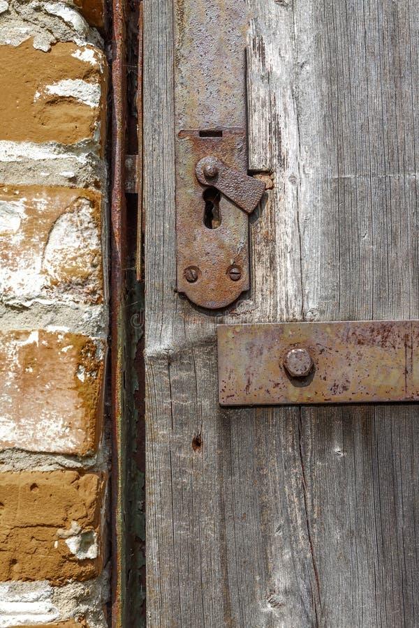 Nyckelhål i en gammal paneled trädörr; rostigt och ridit ut detta arkivfoto