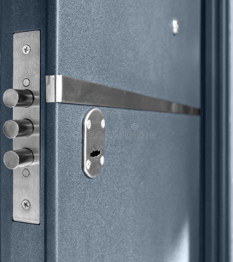 Nyckelhål och bultar på mörker - blå metallisk dörr royaltyfri foto
