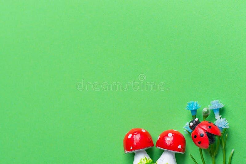 Nyckelpiga för blommor för AmanitachampinjonSmal blått på grön bakgrund som imiterar gräsgrönska Sammansättning från små miniatyr royaltyfria bilder
