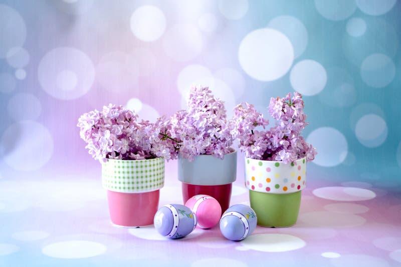Nyckfulla krukor och easter ägg med purpurfärgade lilor royaltyfria foton
