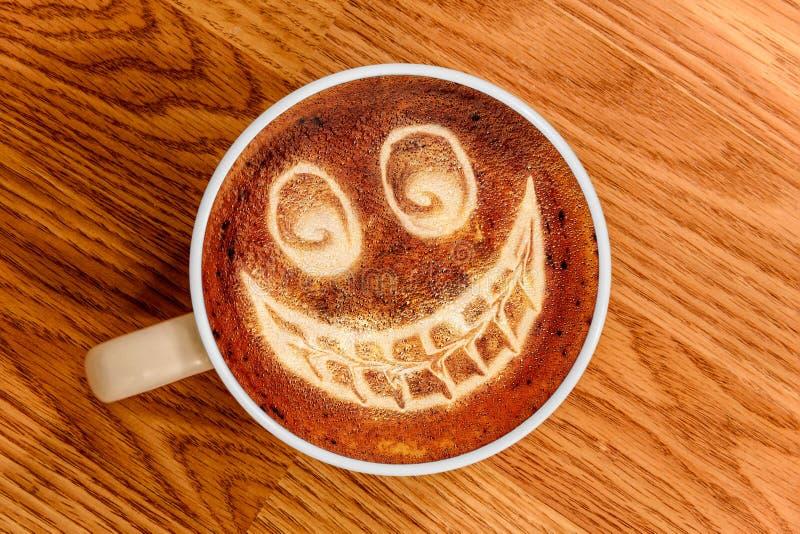Nyckfulla Smiley Face Latte Art på Wood yttersida fotografering för bildbyråer