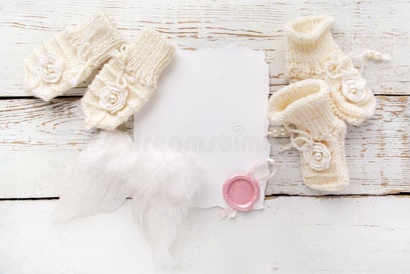 Nyfödd eller dophälsningkort Mellanrumet med behandla som ett barn flickaskor, handskar och vit träbakgrund för ängelwingson arkivbilder