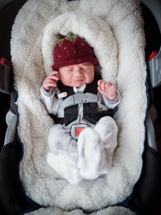Nyfödd pojke i bilsäte fotografering för bildbyråer