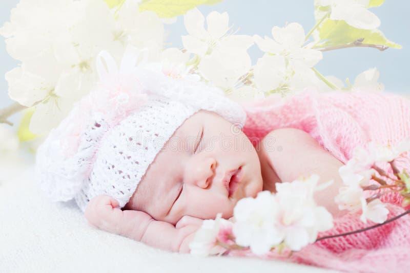 Nyfödda flickasömnar med fjäderblommor fotografering för bildbyråer