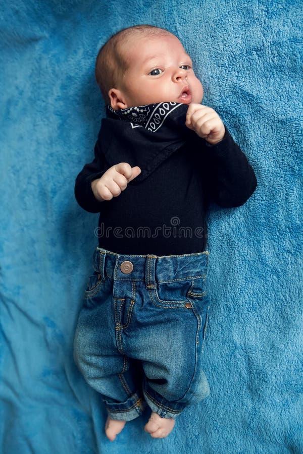 Nyfött behandla som ett barn att ligga i jeans och en svart halsduk royaltyfri foto