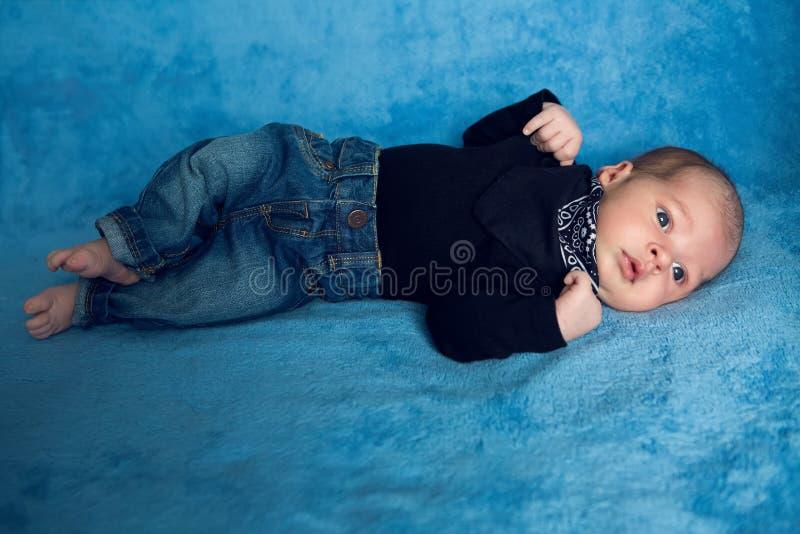 Nyfött behandla som ett barn att ligga i jeans och en svart halsduk arkivfoton