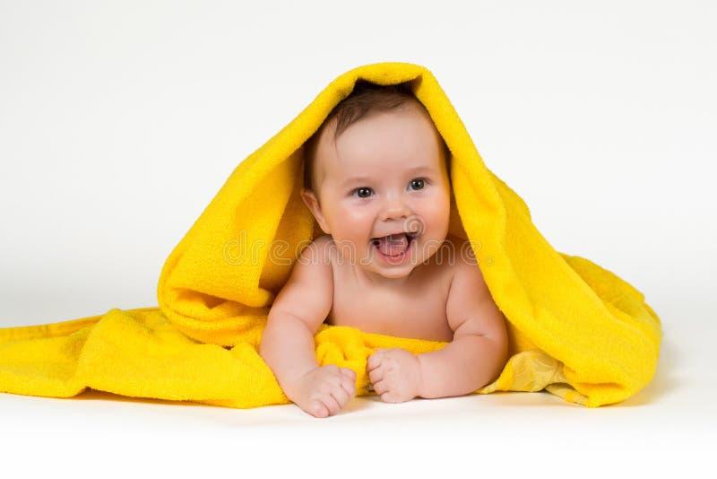 Nyfött behandla som ett barn att ligga ner och att le i en gul handduk fotografering för bildbyråer
