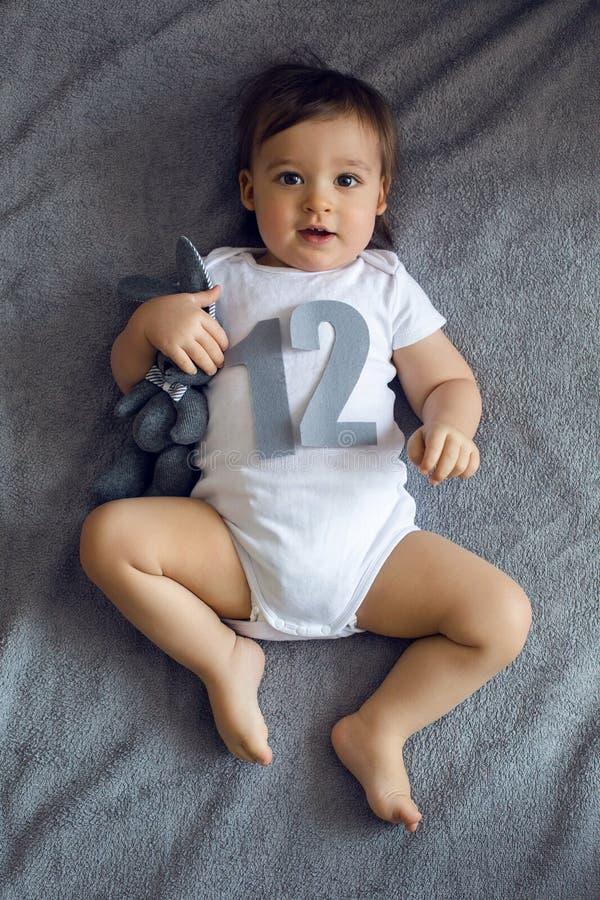 Nyfött behandla som ett barn att ligga på säng med diagram royaltyfria foton