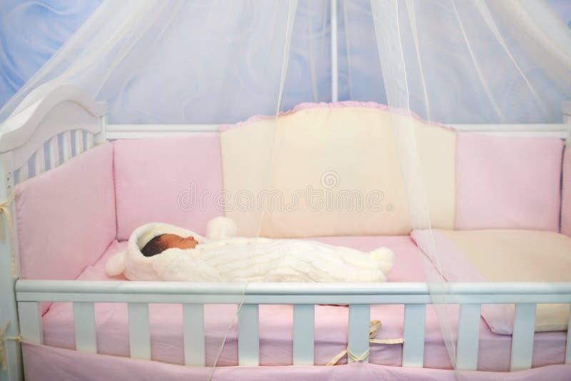 Nyfött behandla som ett barn att sova i en lathund royaltyfria foton