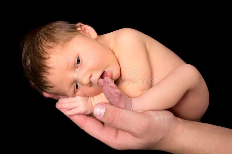 Nyfött behandla som ett barn att suga på tån arkivbild