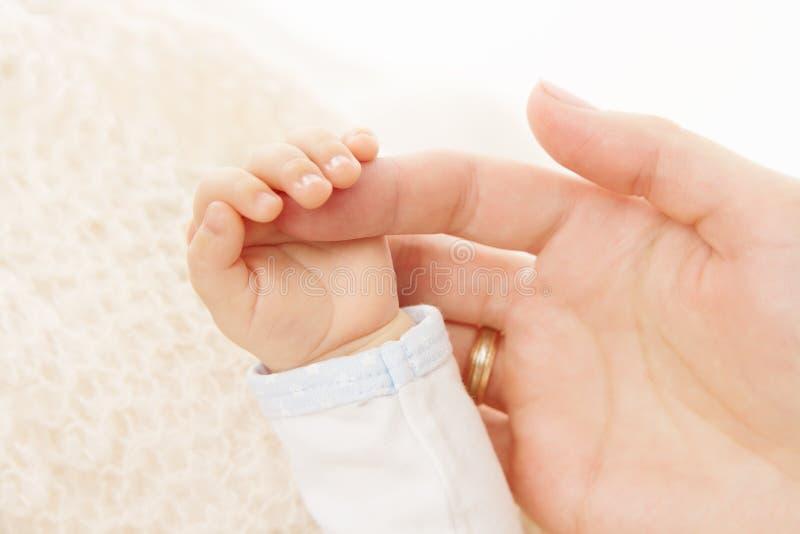 Nyfött behandla som ett barn fingret för handinnehavföräldern royaltyfri bild