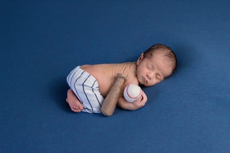 Nyfött behandla som ett barn flåsanden för baseball för pojken bärande enhetliga arkivfoton